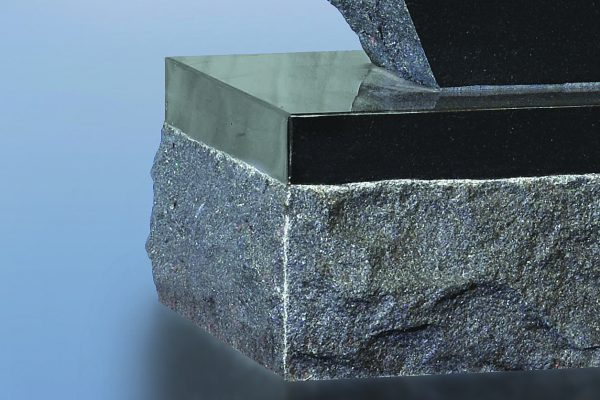 The top of the base along with a 1.5 inch margin along the top is polished; the balance has a rock pitch finish. (Craig p. 6)
